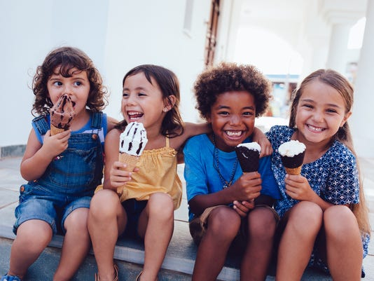 Group of cheerful multi-ethnic children eating ice-cream in summer