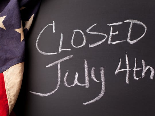 "A ""CLOSED July 4th"" sign handwritten on a black chalkboard with vintage American flag."