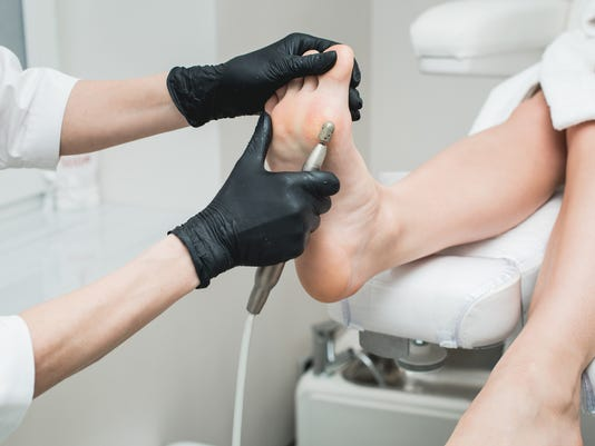 Professional hardware pedicure using electric machine.Patient on medical pedicure procedure,