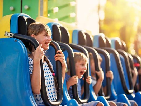 Kids having extreme fun in amusement park drop tower