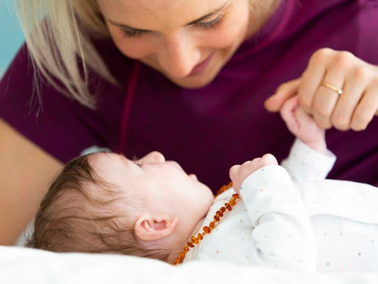 beautiful blond mother with her 3 month old baby wearing a amber necklace