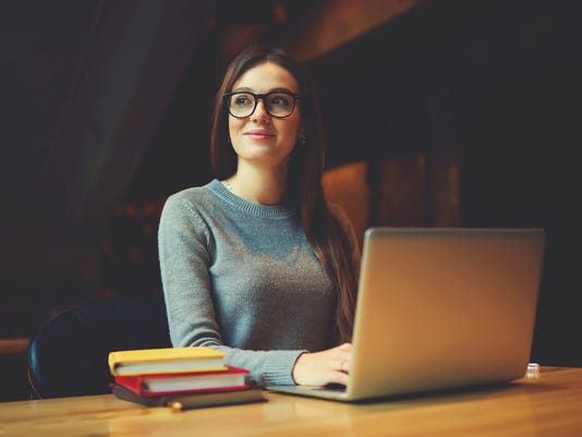 Dreamy attractive female student thinking about coursework strategy