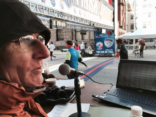 Scott Hubbard, veteran writer for Michigan Runner magazine, announces finishers' names Sunday.