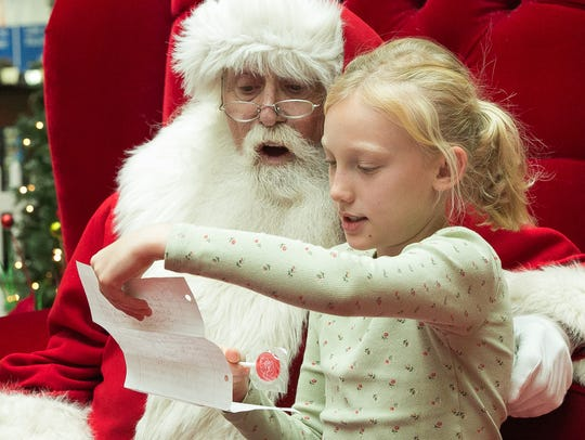Maddie O'Neill, 10, reads each item on her Christmas