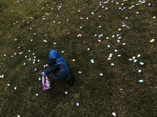Jacob Medrano, 4, of Flint gathers plastic eggs filled with candy during an Easter egg hunt on Friday, March 25, 2016, put on by the Community Impact Church at the Fraternal Order of Police Lodge 126 in Flint.