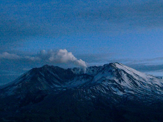 In this March 9, 2005, file photo, Mount St. Helens emits a small, steady cloud of steam at dusk in Washington state. The 2018 eruption of the Kilauea volcano in Hawaii has geologic experts along the West Coast warily eyeing the volcanic peaks in Washington, Oregon and California, including St. Helens, that are part of the Pacific Ocean's Ring of Fire.
