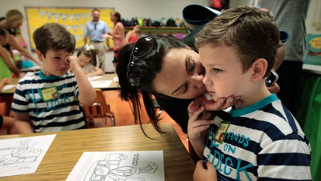 August 4, 2014 -  Lori Harris makes her bitter-sweet goodbyes to her twins Jacob (right) and Joshua as they start kindergarten at Dogwood Elementary Monday morning, the first day of the new Germantown Municipal School District. (Jim Weber/The Commercial Appeal)