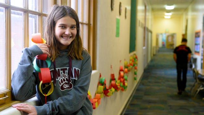 Karsen Dane, a seventh-grader at Our Lady of Lourdes, stands with a prayer chain made for her by schoolmates while she was in the hospital with a sinus infection that made its way into her brain and nearly killed her.