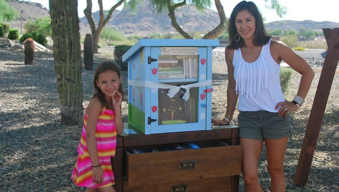 Anna Wolcott, 6, and her mother, Heather, stand by the Little Free Library that Anna spent weeks building and decorating for their Ahwatukee home. The library was recently stolen, according to Heather.