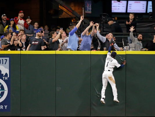 Seattle Mariners center fielder Jarrod Dyson watches fans grab for a home run by Los Angeles Angels' Mike Trout during the sixth inning of a baseball game Wednesday, May 3, 2017, in Seattle. (AP Photo/Elaine Thompson)