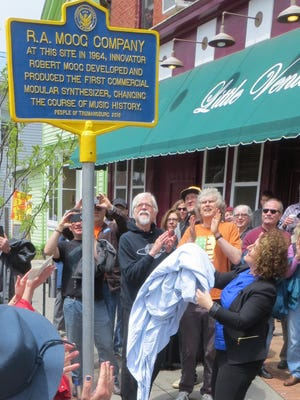 Michelle Moog-Koussa, daughter of Robert Moog, unveils a historical marker Sunday in front of the former location of R. A. Moog Co., at 49 E. Main St. in Trumansburg. In the immediate background are two of her father's friends and colleagues, David Borden, left, and Trevor Pinch, in orange T-shirt.
