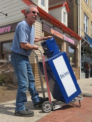 In this April 22, 2016 file image, Steve Oh, a driver for North Jersey Media Group, carts away one of last news boxes in Millburn for The Item of Millburn and Short Hills.