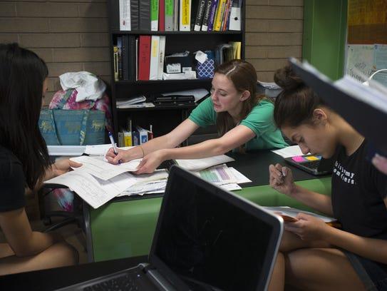 Chemistry teacher Lauren Cooney (center) works with