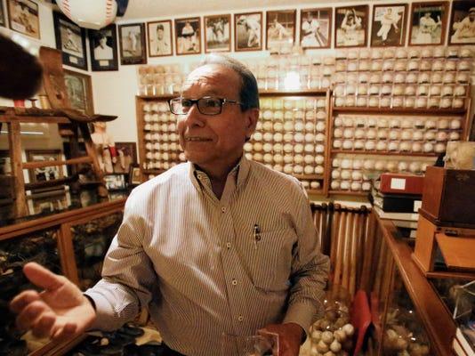 Collector Fernando Grado tosses a vintage baseball in his baseball memorabilia room.
