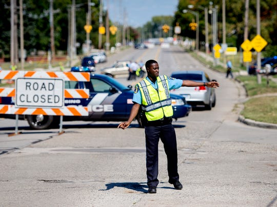 A Lansing police officer directs traffic off South