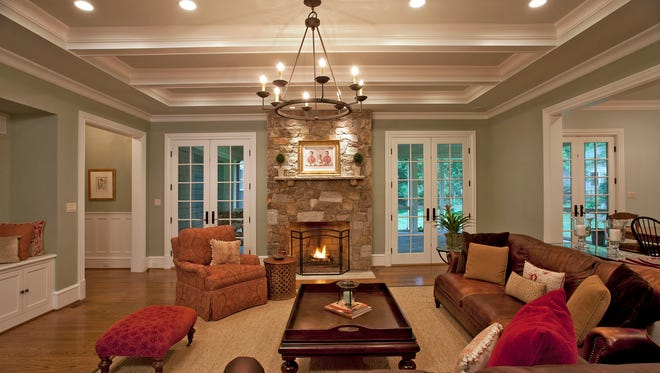 The central family room features a stone fireplace, beams within the coffered ceiling, two sets of French doors to the screened porch along the back of the home, and a connection to the kitchen. MUST CREDIT: Ken Wyner.