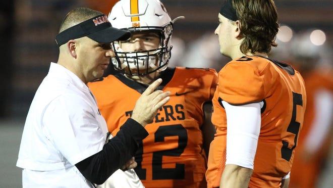 Massillon quarterbacks coach/co-offensive coordinator Jarrett Troxler talks to Tiger quarterbacks Zach Catrone (12) and Aidan Longwell (5) during the Week 7 win over Gateway (Pa.) last season.