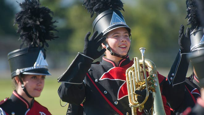 A member of Riverheads' marching band waves to the crowd at the end of their performance during the Blast in the Draft competition at Stuarts Draft High School on Saturday, Sept. 27, 2014.