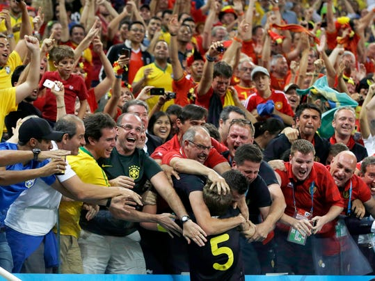 Belgium's Jan Vertonghen is swarmed by supporters after scoring his side's first goal during the group H World Cup soccer match between South Korea and Belgium at the Itaquerao Stadium in Sao Paulo, Brazil, Thursday, June 26, 2014. (AP Photo/Thanassis Stavrakis)