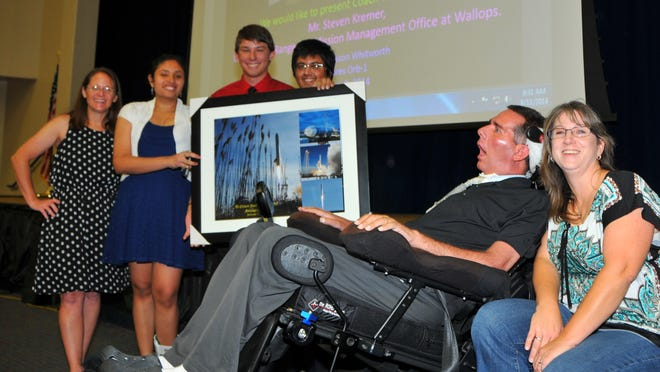 Jason Whitworth, a former teacher with ALS, came to West Shore Jr./Sr. High on Monday for a special presentation. As part of the welcome-back teachers' festivities, Whitworth was given a large photo of the launch that carried students' experiment on ALS to the space station. Teacher Amy McCormick and former students Robert Edmiston, Sanju Vardhan and Harshit Saini are with Whitworth and his wife, Gayle.