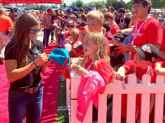 NASCAR Sprint Cup driver Danica Patrick signs autographs for fans outside the Media Center on Sunday morning of race day.