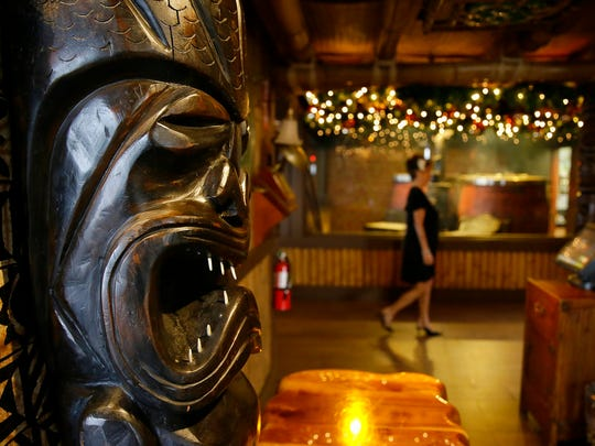 In this photo taken Saturday, Dec. 2, 2017, Claudette Lum, 80, walks past the Chinese wood fired ovens at Trader Vic's in Emeryville, Calif. After 57 years as a hostess and maitre d', Lum is retiring at the end of the year.