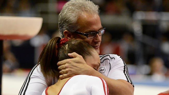 Jordyn Wieber gets a hug from coach John Geddert during a competition in 2012.