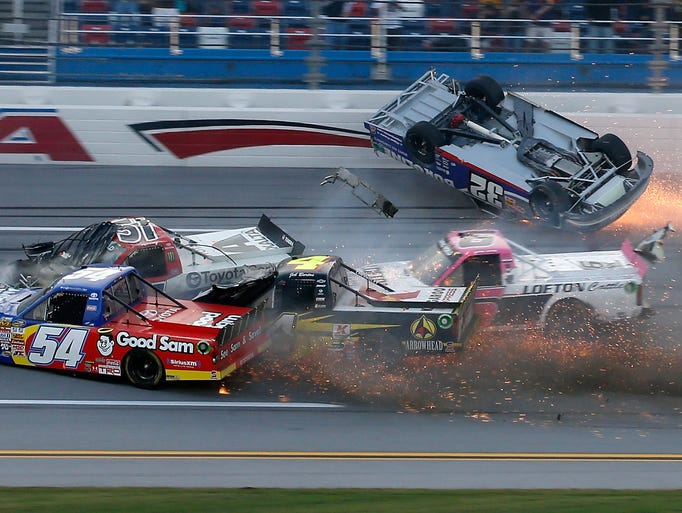 Miguel Paludo (32) slides down the track on his roof as Darrell Wallace Jr. (54), Jeb Burton (4), Justin Lofton (6), and Kyle Busch (51) crash on the last lap of the Camping World Truck Series Fred's 250.