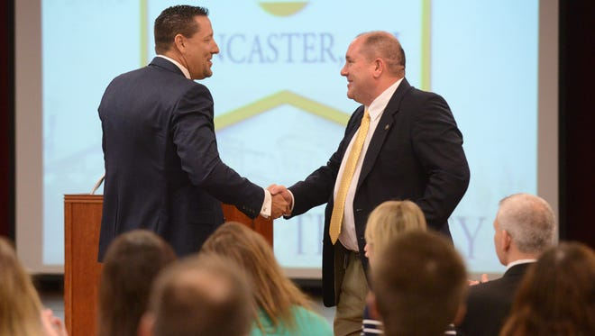 Lancaster Mayor Brian Kuhn, right, shakes hands with Adam Grzybicki at the state of the city address Wednesday at Olivedale Senior Center in Lancaster. Grzybicki, president of AT&T Ohio announced the company was installing fiber optic runs to Rock Mill Industrial Park.