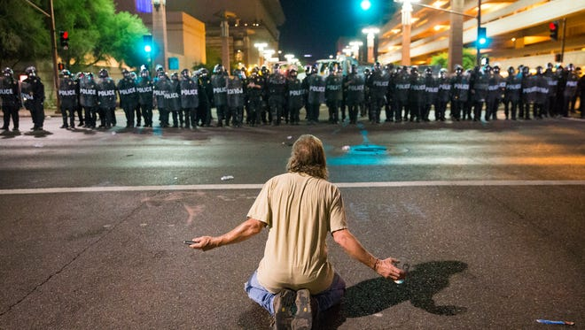A protester sits on Second St. in front of Phoenix Police trying to clear the area around the Phoenix Convention Center. Michael Chow/The Republic
