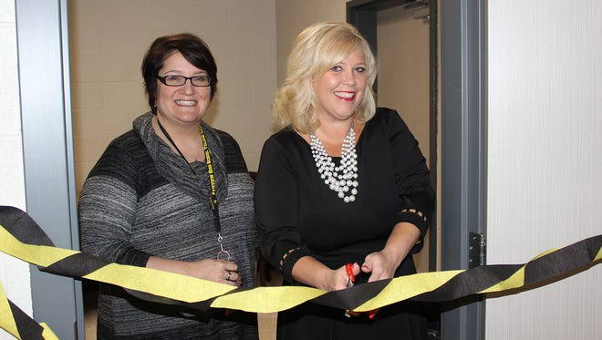 Fairview High School Assistant Principal Ellen Browne joins Holly Black, affiliate broker with Parks Realty, in cutting the ribbon on the new FHS teachers lounge.