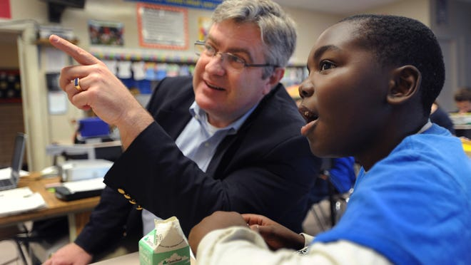Laurel Superintendent John Ewald, shown with Laurel Intermediate Middle School sixth-grader Ivory Miller in 2013, is being replaced by a new superintendent, Shawn Larrimore.