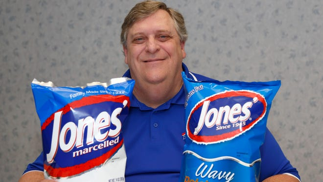 Bob Jones, the CEO for Jones Potato Chip Co., holds two bags of potato chip. On the left is the original chips that are fried in partially hydrogenated oil, while on the right is fried with corn or cottonseed oils.