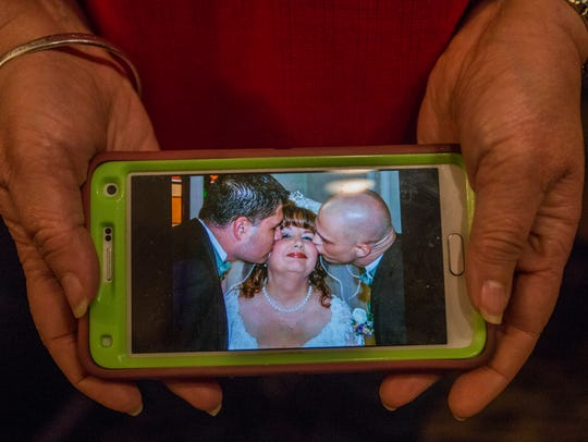 Renea Rosson holds a photo from her wedding day that