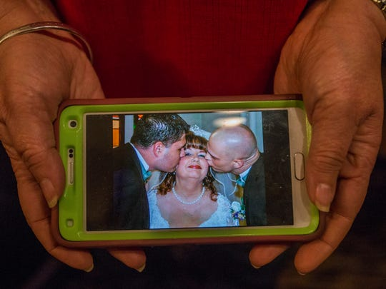 Renea Rosson holds a photo from her wedding day that shows her two sons, Derick and Tim, kissing her on the cheek.