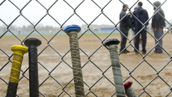 Softball officials call for a rain delay at Tuesday's game between Rice and Essex High Schools on April 22, 2014.