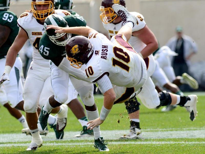 Michigan State's Darrien Harris (45) tosses CMU's Cooper Rush (10) to the ground in the second quarter of play Saturday, September 26, 2015 at Spartan Stadium.