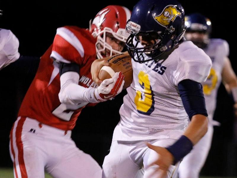 Laingsburg's Cole Blankenship, left, strips the ball from Pewamo-Westphalia's Ryan Smith Friday, Oct. 9, 2015, in Laingsburg, Mich. The ball was recovered by P-W. Pewamo-Westphalia won 50-7.