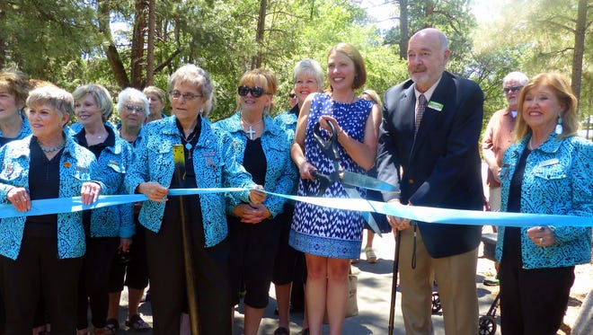 New Mexico Tourism Cabinet Secretary Rebecca Latham cuts the ribbon on river restoration project at Two Rivers Park. Next to her is Ruidoso Mayor Tom Battin. The two are flanked by Ruidoso Valley greeters.