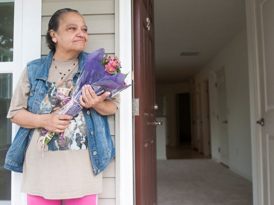 Elida Echevarria stands by the front door of her new home Wednesday after a ribbon-cutting ceremony that welcomed her and her son, Louis Lopez, into their new home in the newly redeveloped Mount Holly neighborhood formerly known as Mount Holly Gardens.