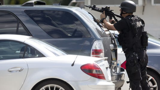 An officer points his weapon near the scene of a shooting at Mercy Fitzgerald Hospital in Darby, Pa.