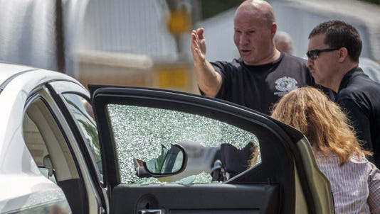 Law-enforcement officers look over a highway patrol vehicle that had its window shot out in Fayetteville, N.C.