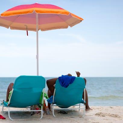 Beachgoers sit near the Naples pier on Wednesday, July
