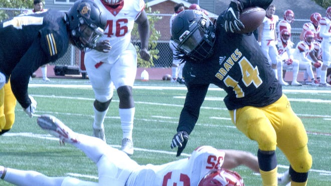 Ottawa University running back Derrick Curtis avoids a tackle by a McPherson defender Saturday in the Braves' victory. Curtis rushed for 255 yards and scored three touchdowns.