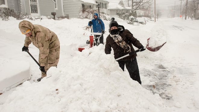 As the blizzard rages Saturday, homeowners shovel their driveway in the Wanamassa section of Ocean Township on January 23, 2016.