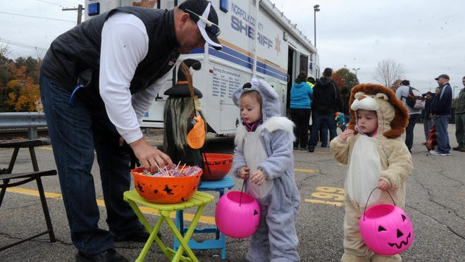 FILE - From left, Michael Silva, hands out candy to Ryan Gover, 2, and tiwn sister Brooklyn. Stoughton police held its annual safe trick-of-treating tours at the station and other downtown buildings in 2015. The CDC says offering individually wrapped, grab-and-go candy bags in 2020 would be a safer alterntaive during the ongoing COVID-19 pandemic.