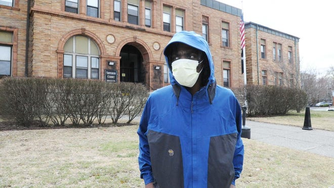Kesone Jones, of Brockton, walks in the area of Brockton Superior Court while wearing a mask during the coronavirus pandemic on March 24, 2020.