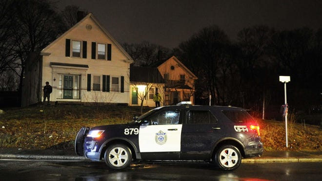 A police cruiser idles outside a home on Brockton's Ames Street.