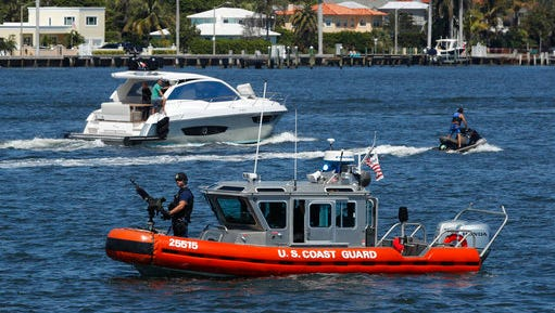 FILE - In this March 19, 2017 file photo, U.S. Coast Guard patrol Lake Worth Lagoon as President Donald Trump returns to his Mar-a-Lago estate in Palm Beach, Fla. It's widely estimated that each trip to the resort costs taxpayers $3 million, based on a government study of the cost of a 2013 trip to Florida by President Barack Obama. But that trip was more complicated and the study's author says it can't be used to calculate the cost of Trump's travel. This weekend, Trump is making his seventh visit to Mar-a-Lago since becoming president.