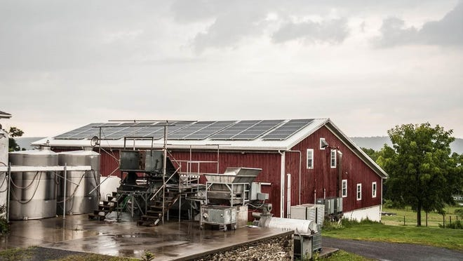 Winemaking equipment is in the foreground and solar panels can be seen on the roof of a Hunt Country Vineyards building.